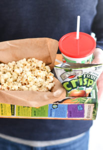 Hands holding a DIY Popcorn Box with a drink and snack