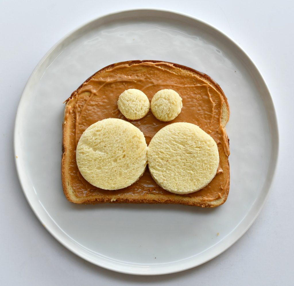 A plate with a piece of toast with peanut butter over it and 2 bread circles for cheeks and 2 for eyes.