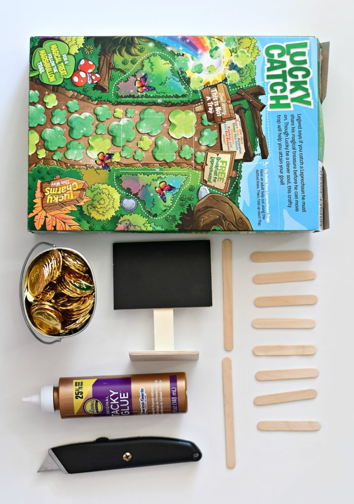 All the supplies needed for a DIY leprechaun trap: a cereal box, pot of gold, glue, a mini chalkboard sign, and popsicle sticks.