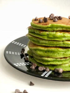 A stack of green mint chocolate chip pancakes