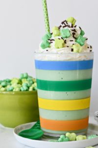 A rainbow striped cup filled with a healthy green Shamrock Shake with whipped cream and sprinkles.