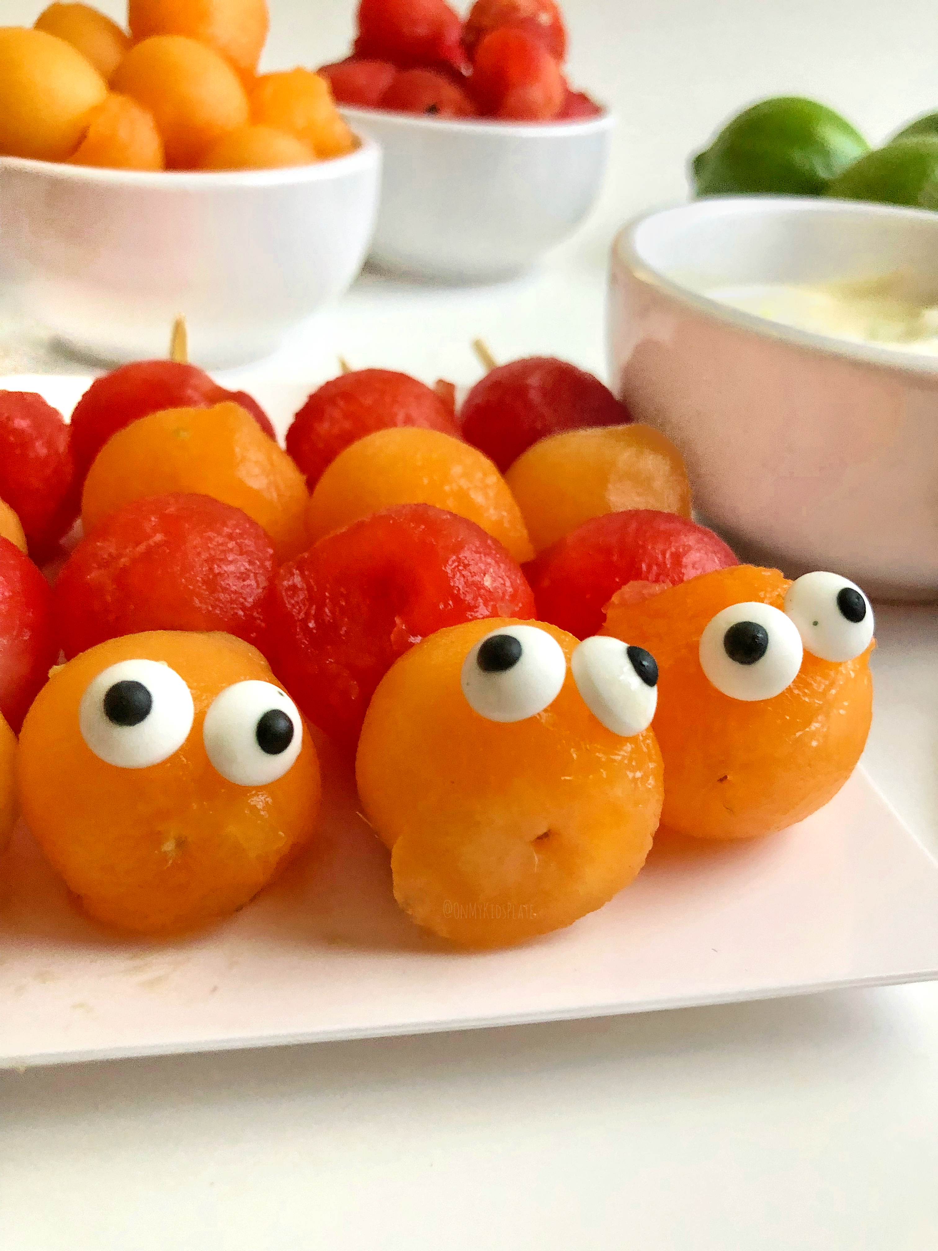 Cute pre-made Caterpillar Fruit Kebabs, ready for dipping