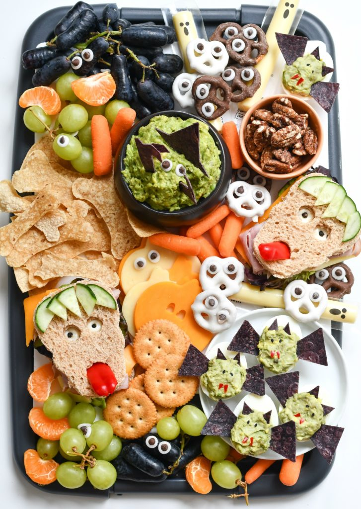 A black platter filled with fun, easy Halloween snack ideas like monster sandwiches and deviled bat eggs.